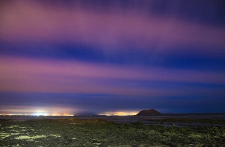 northern Fuerteventura, long exposure night shot towards isla de Lobos and Lanzarote, blurred clouds and star trails photo