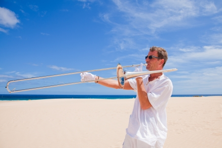all weather: tanned man in white playing silver trombone in the dunes by the ocean