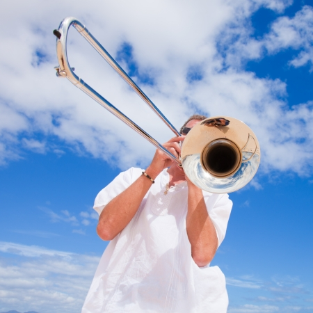 tanned man in white playing silver trombone in the dunes photo