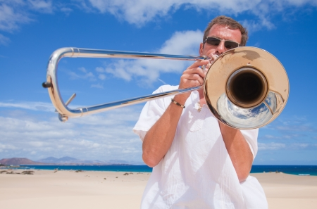 all weather: tanned man in white playing silver trombone in the dunes of Corralejo
