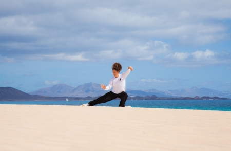 Young attractive woman making Thai-chi movements in the dunes by the ocean photo