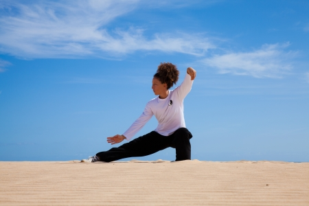 taichi: Young attractive woman making Thai-chi movements in the dunes by the ocean