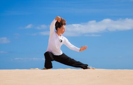 Young attractive woman making Thai-chi movements in the dunes by the ocean