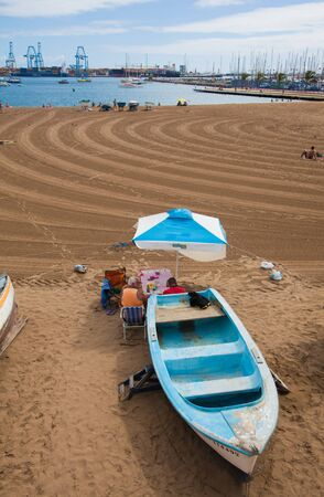 canarias: Las Palmas de Gran Canarias, sunday on a town beach, people enjoy themselvves undeterred by industrial port background