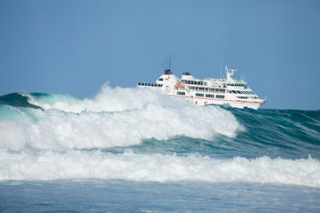 Sea swell and ferry - ARMAS ferry going from Lanzarote to Fuerteventura, large waves on the foreground Stock Photo - 15942826