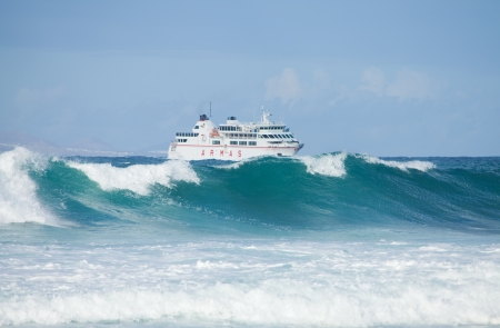 swell: Sea swell and ferry - ARMAS ferry going from Lanzarote to Fuerteventura, large waves on the foreground Editorial