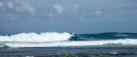 group of surfers in the sea swell off northern coast of Fuerteventura, Lanzarote in the background