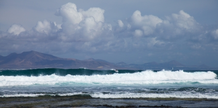 swell: group of surfers in the sea swell off northern coast of Fuerteventura, Lanzarote in the background Editorial
