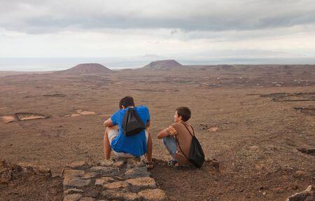 hondo: Northern Fuerteventura, overcast day, two boys resting on the edge of Calderon Hondo Stock Photo