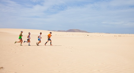 CORRALEJO - NOVEMBER 03: Participants running in the dunes at Fourth international Fuerteventura half-marathon 03 November, 2012 in Corralejo, Fuerteventura, Spain Stock Photo - 16224665
