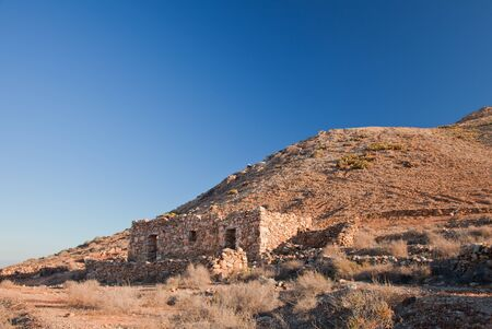 Fuerteventura, mount Tindaya, ruins of a traditional stone house at the bottom of the slope photo
