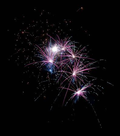 few fireworks exploding against black background photo