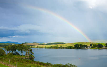 scottish landscape with clouds and rainbow over lake photo