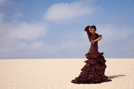 Flamenco dancer in the long dress in the dunes