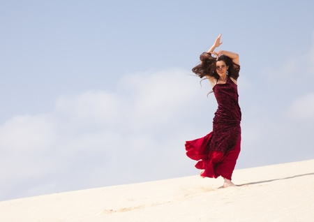 Flamenco dancer in the long dress in the dunes photo