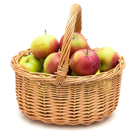 willow fruit basket: wicker basket full of apples isolated on white Stock Photo