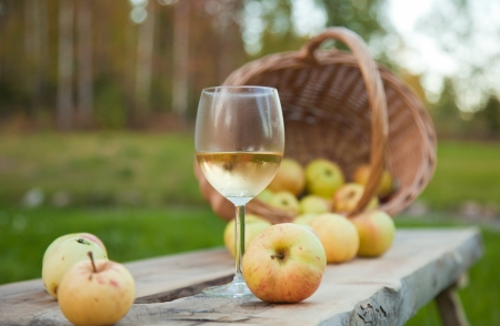 apple cider in a chilled wine glass, rustic settings with apples and wicker basket photo