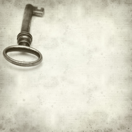 textured old paper background with old rusty  key photo