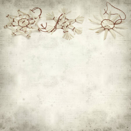 textured old paper background with traditional straw Christmas ornaments photo