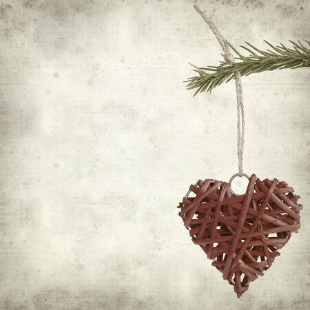 textured old paper background with red straw heart photo