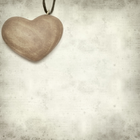 textured old paper background with wooden heart pendant photo