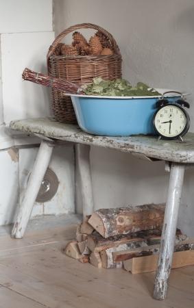 kindling: sauna time  - still life with enamelled tub, sauna besom, kindling, firewood and alarm clock