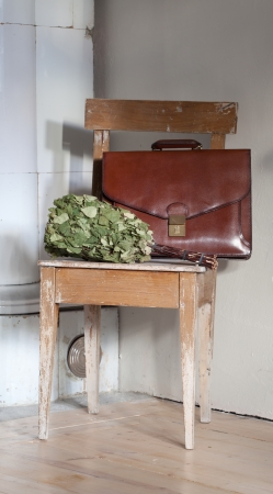 going to sauna after work - still life including old leather briefcase and birch branch twigs besom for sauna photo
