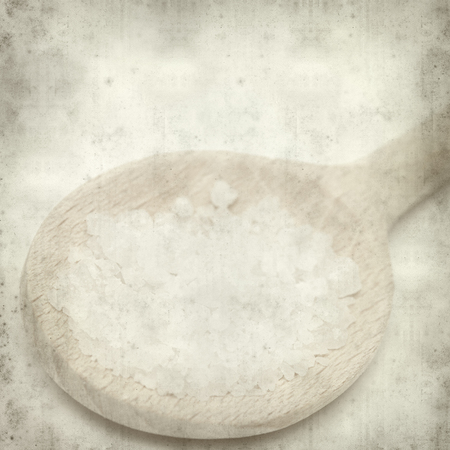 textured old paper background with wooden spoon with rock salt photo