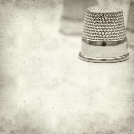 textured old paper background with thimbles photo