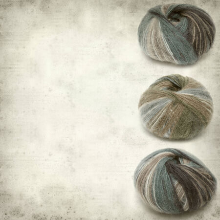 textured old paper background with variegated knitting wool photo