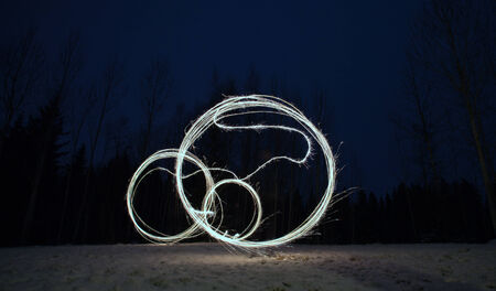 sparkler games - impossible bicycle drawn in the air by sparkler stick, wintry background photo