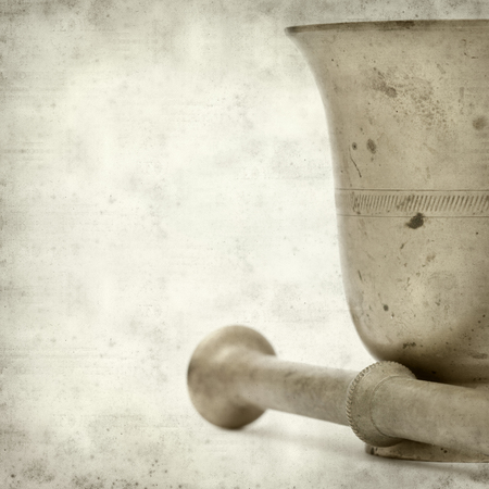 textured old paper background with copper mortar and pestle photo