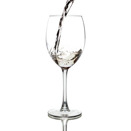 white wine pouring into a glass, isolated on white photo