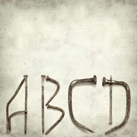 textured old paper background with forged nail letters partial alphabet photo