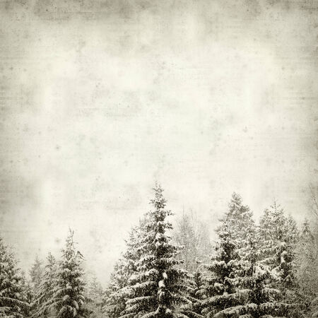 textured old paper background with trees under snow