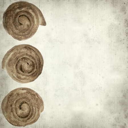 textured old paper background with scandinavian cinnamon bun photo