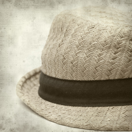 textured old paper background with old broken panama straw hat photo
