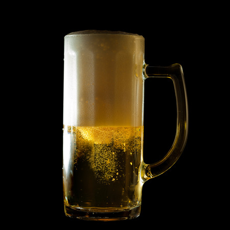 overflowing beer mug isolated on black photo