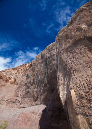 steep cliffs: North West of Gran Canaria, steep cliffs along the coasts covered with netting to protect and prevent falling stones Stock Photo
