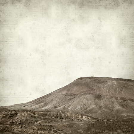 textured old paper background with Montana Roja, red Mountain, of Fuerteventura photo