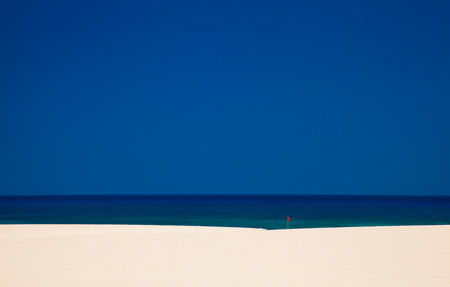 blue background: Fuerteventura, Burro Beach with red no swimming flag, raising heat melts the air above sand