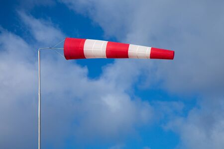 strong wind: windsock indicating strong wind on blue sky with light clouds background Stock Photo