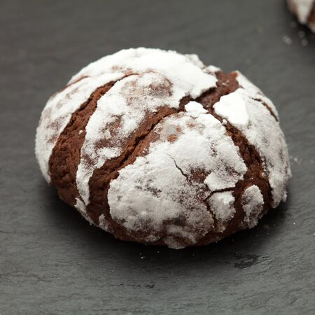 trivet: freshly made chocolate biscuits coated in icing sugar on a slate trivet