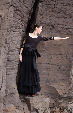 Flameco dancer in a basalt ravine, the rocks reachly textured