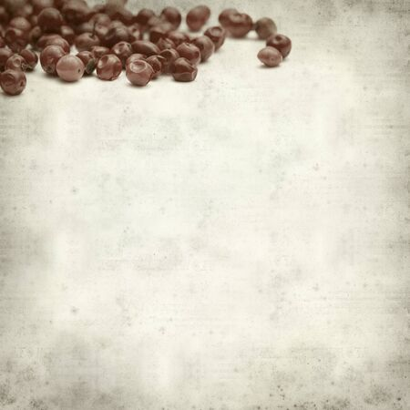 textured old paper background with pink peppercorns photo