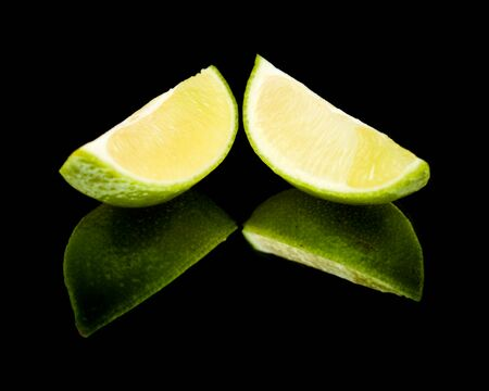 quartered: lime fruit on black mirror, isolated
