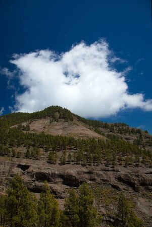 ghostlike: Inland Gran Canaria, eroded soft rock mountain, ghost-like cloud over it Stock Photo