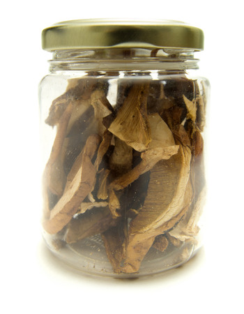 intense flavor: Dried porcni mushroom slices in a storage jar isolated on white background