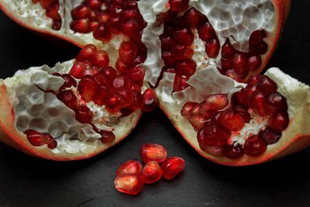 trivet: open pomegranate and scattered seeds on black slate trivet