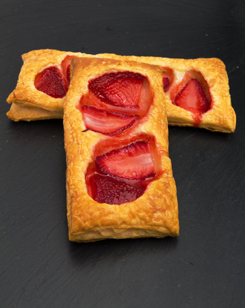 trivet: puff pastry slices with strawberry on black slate stone surface